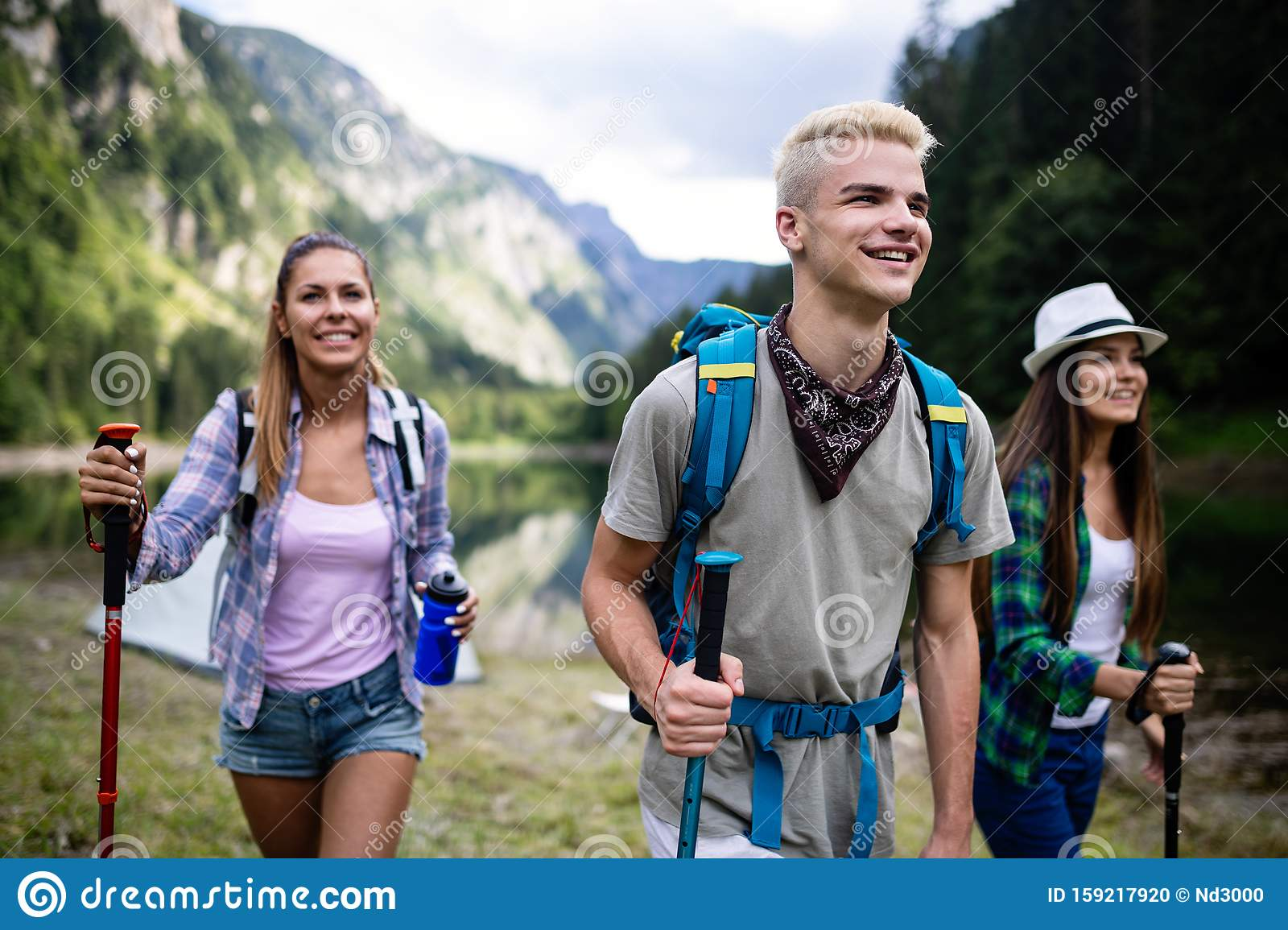 Smiling Friends Walking With Backpacks Adventure Travel Tourism Hike And People Concept Stock Photo Image Of Destination Lifestyle 159217920