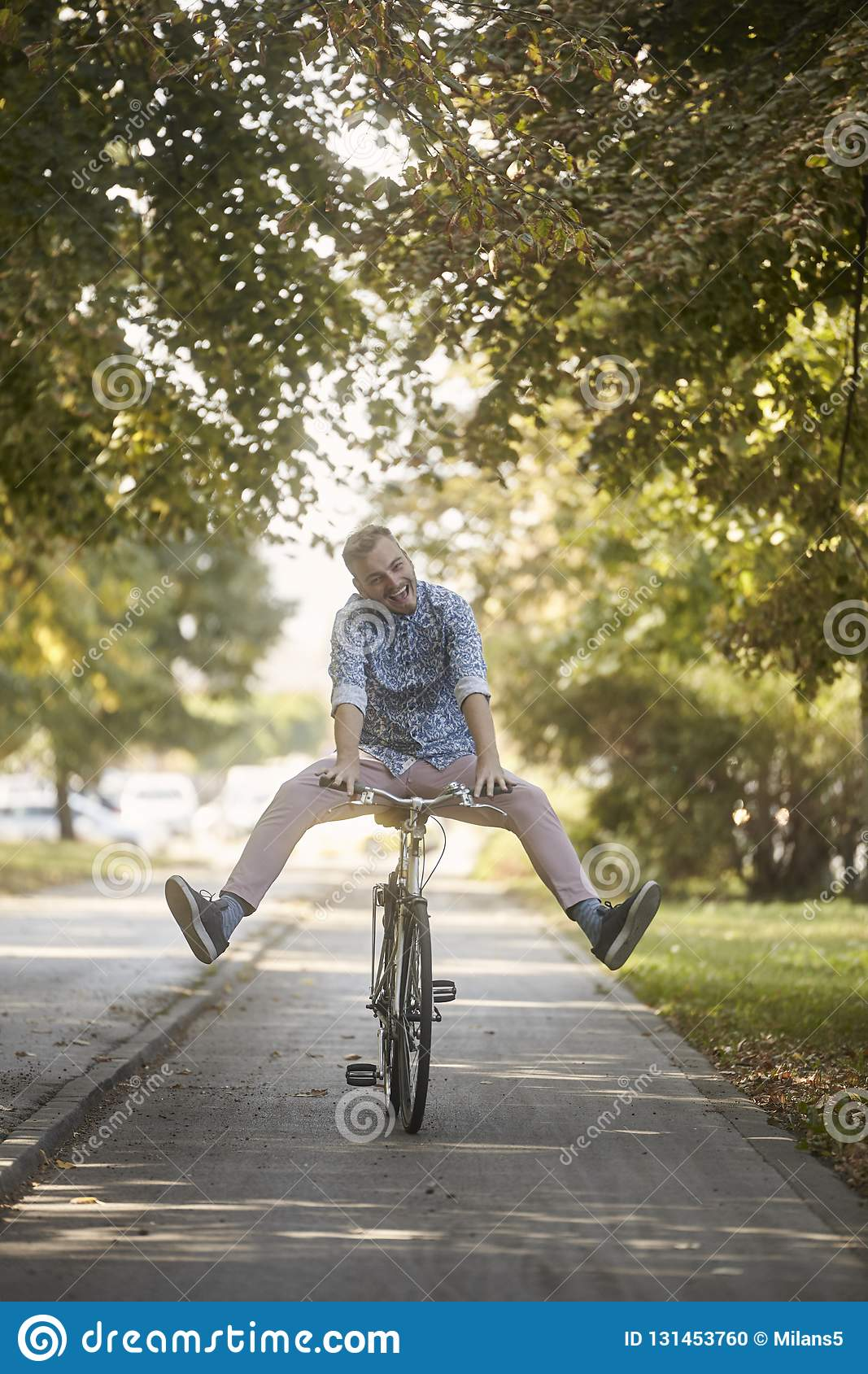 Smiling, funny, ridiculous, young man, 20-29 years old, cycling on road track. legs spread