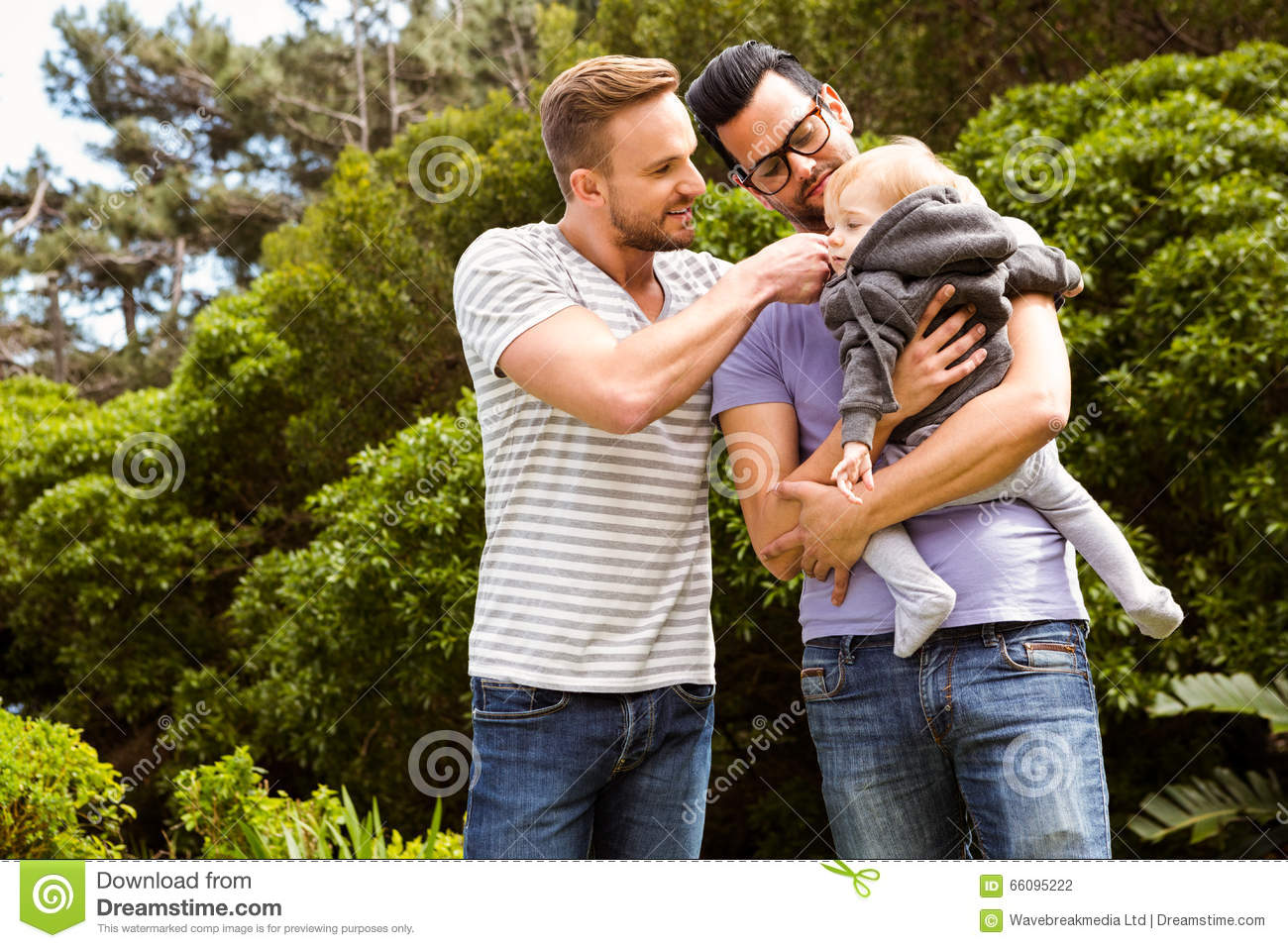 Happy adult gay couple embracing in nature in the evening