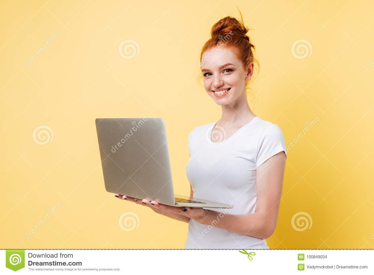 Smiling ginger woman in t-shirt holding laptop computer
