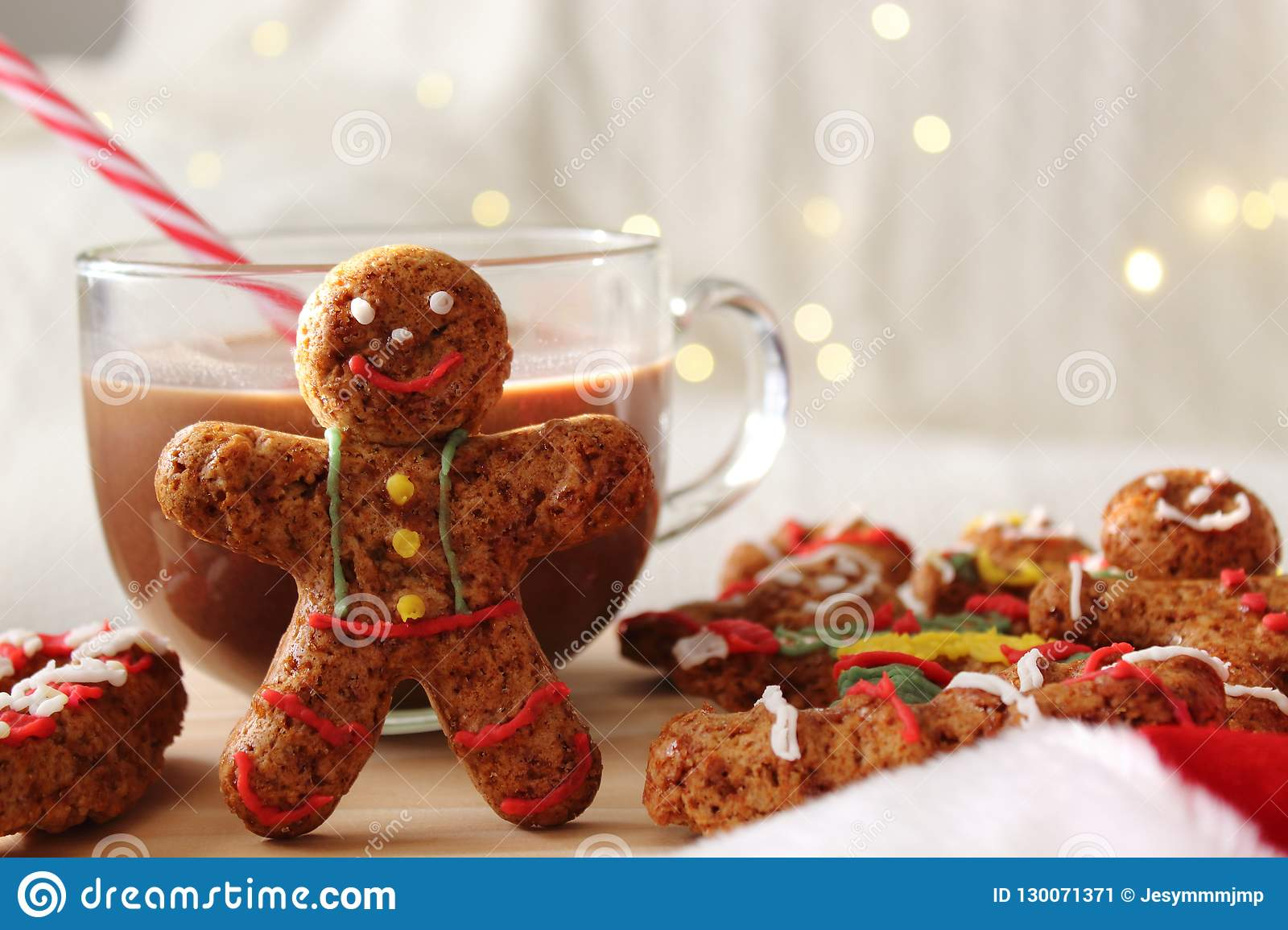 Smiling gingerbread man standing next to chocolate mug. Table of additional cookies.