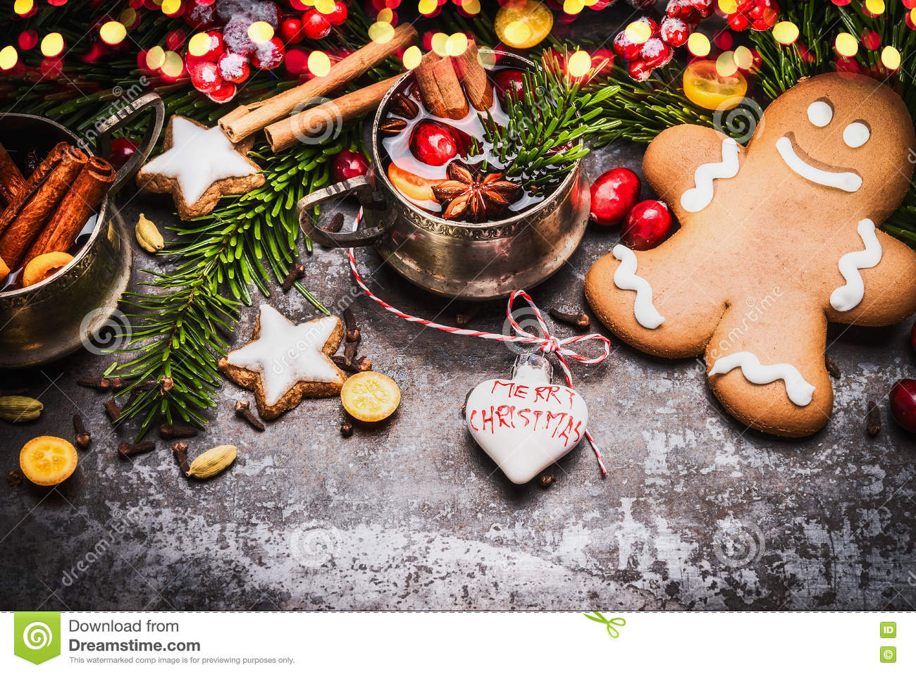 Smiling gingerbread men with mug of mulled wine , Christmas decoration and holiday cookies and spices on dark rustic background wi