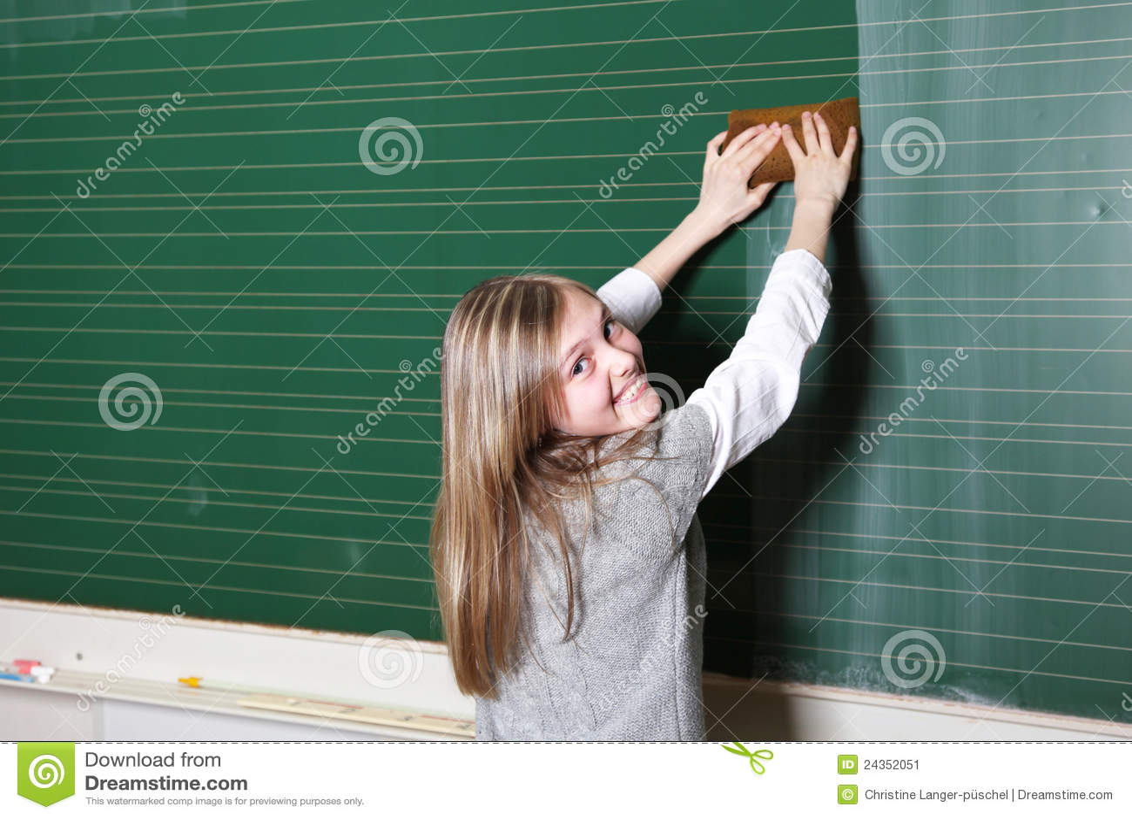 Smiling Girl Cleaning School Blackboard Stock Image
