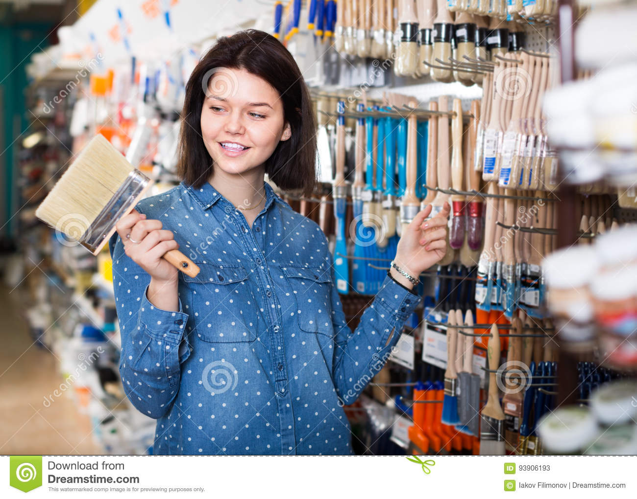 Smiling Girl Deciding On Brush For Decorating House In Paint