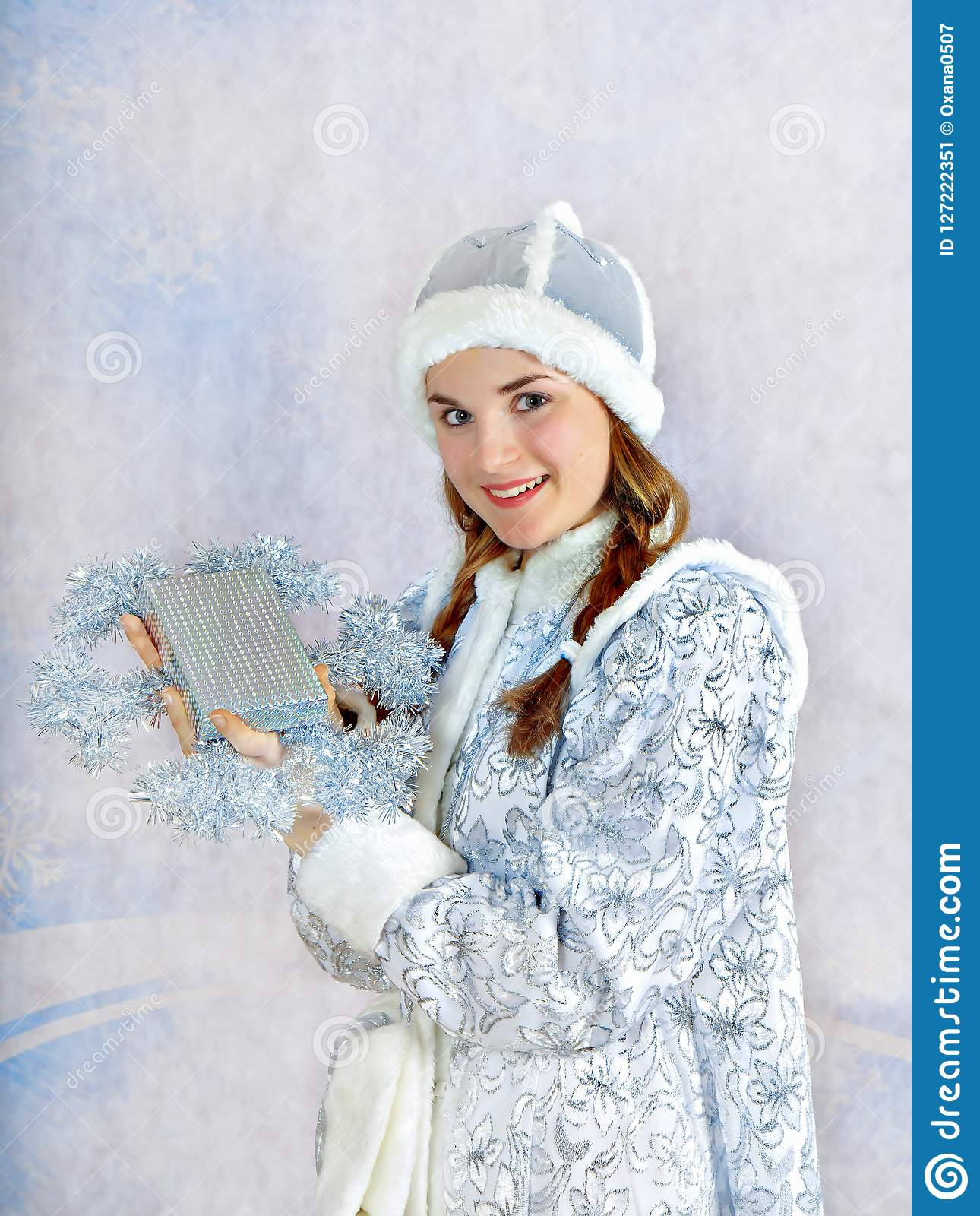Smiling girl dressed in traditional russian christmas costume of Snegurochka Snow Maiden with present box,