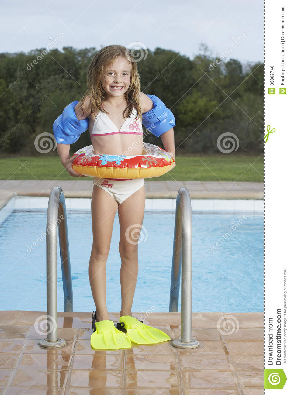 smiling girl with inflatable ring and fins against pool