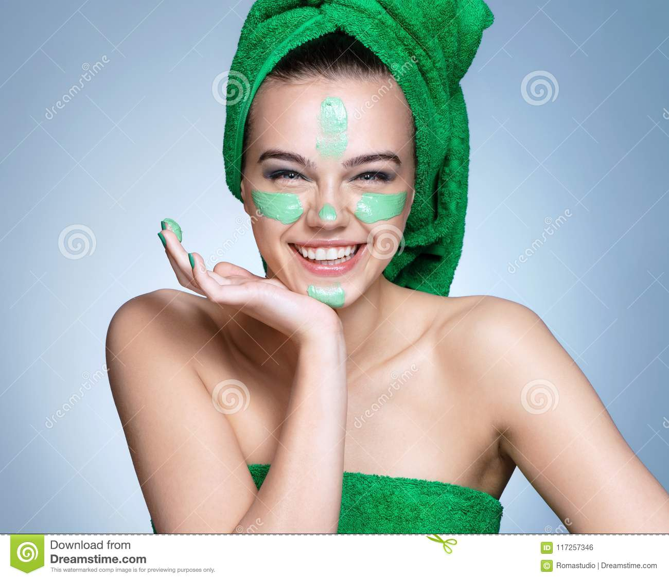 Smiling girl with moisturizing cream on her face.
