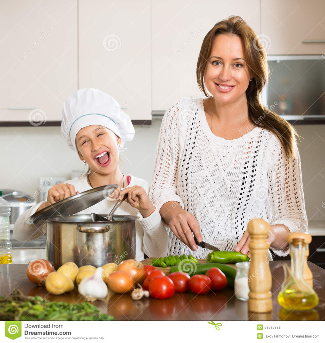 Smiling Girl And Mom At Kitchen Stock Image
