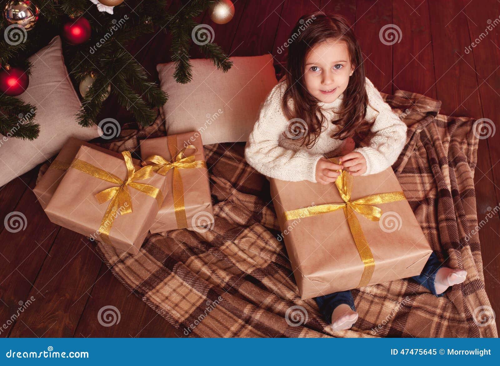 Smiling girl opening christmas presents Girl Opening Christmas Presents Stock Image - of