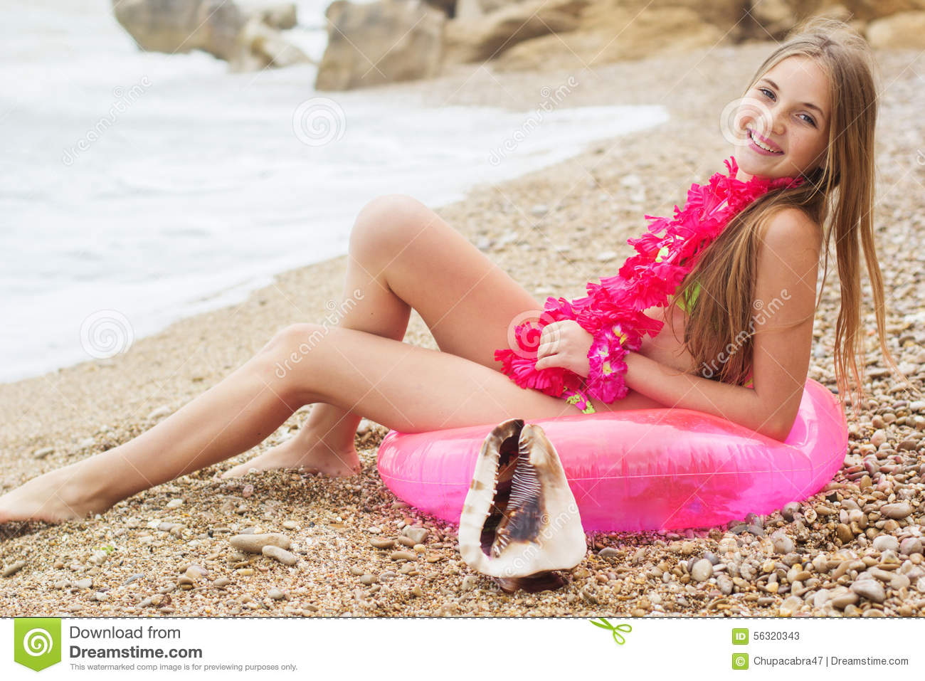 Cute smiling teen girl wearing swimsuit and pink flowers on her neck is  sitting at beach on pink rubber ring, summer time