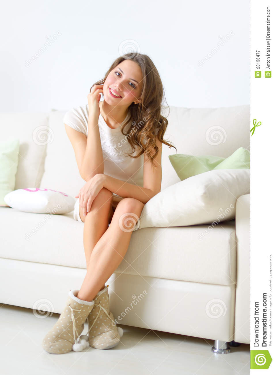 Smiling Girl Sitting On Sofa Royalty Free Stock