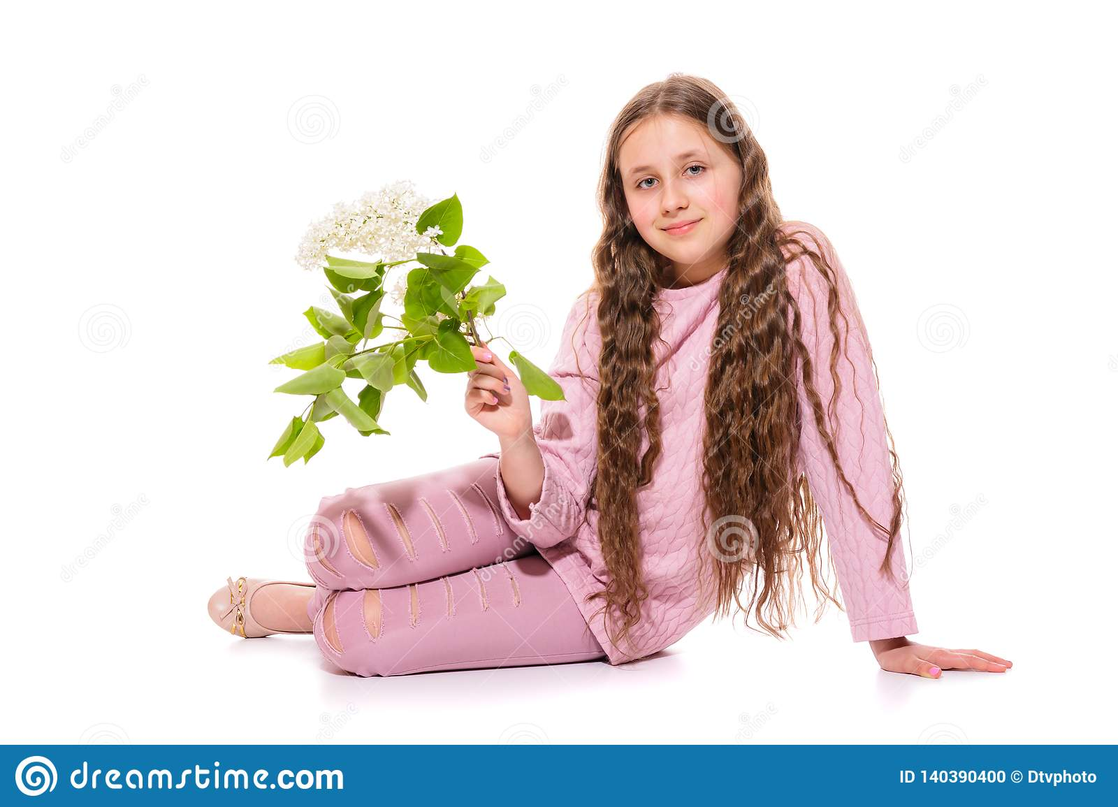 Smiling girl 10-11 years old in a pink suit holding white lilac in her hands. Isolation on a white.