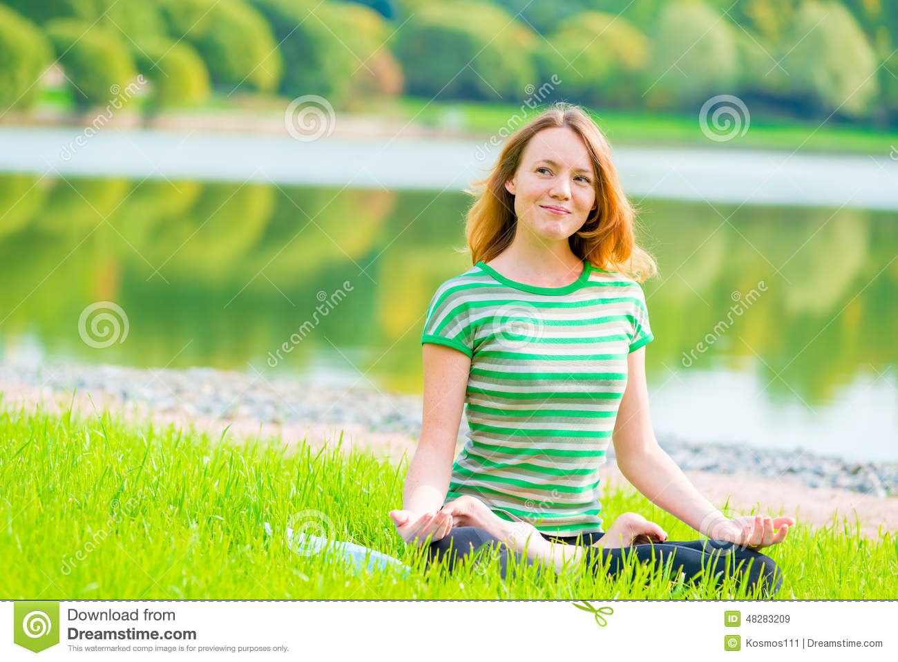 Smiling girl-yogi performs exercises in a green park