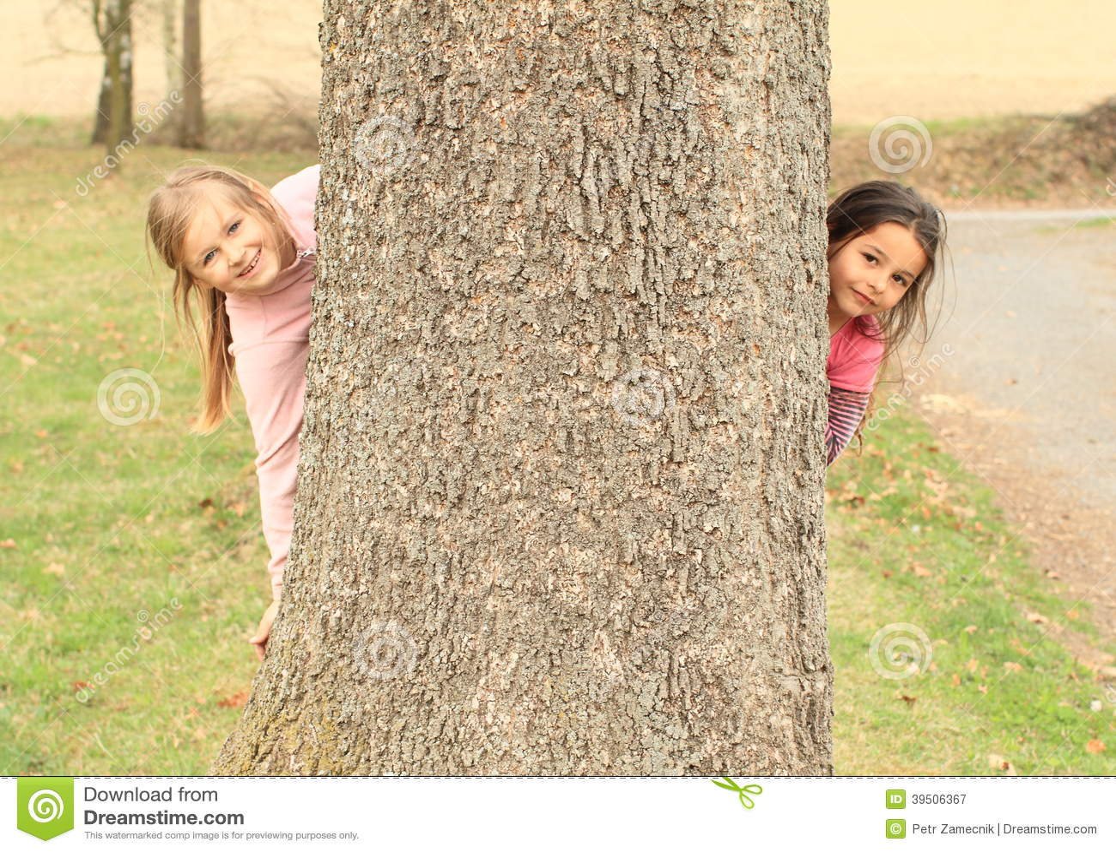 Smiling girls hiding behind tree