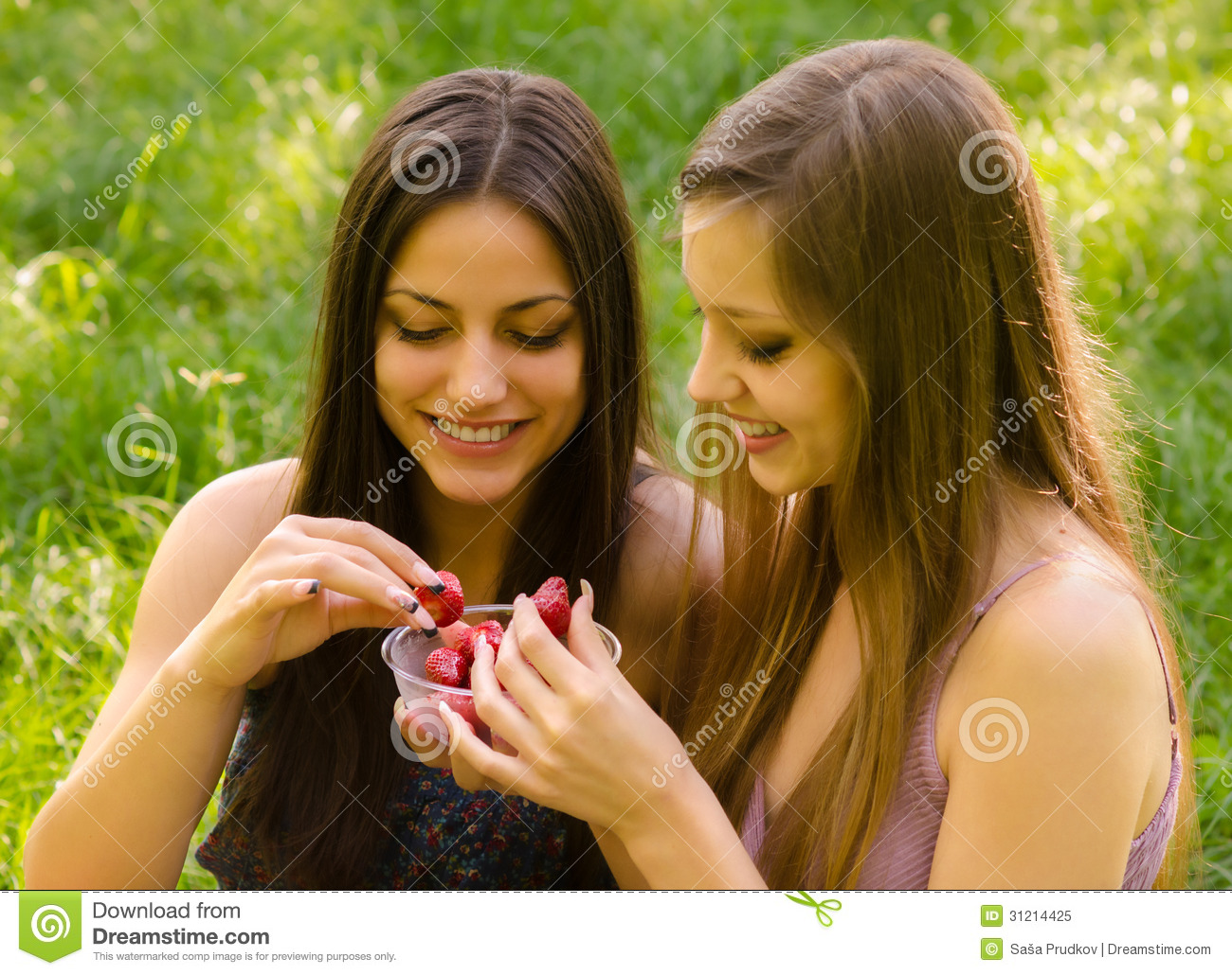 smiling girls sharing strawberries outdoor royalty free