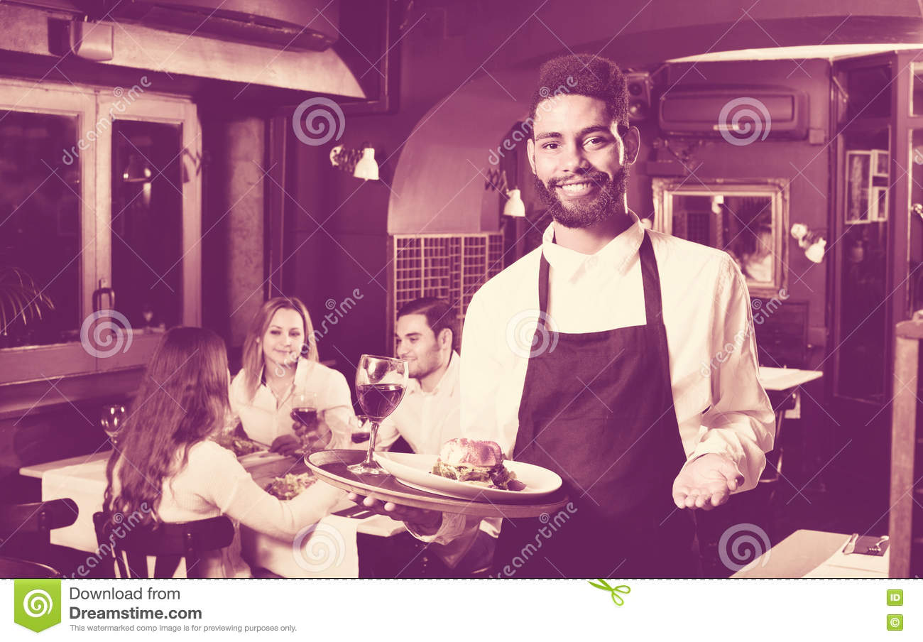 Smiling Glad Waiter Taking Care Of Adults Stock Photo