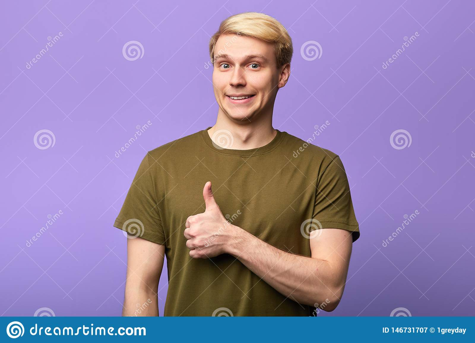 Smiling gorgeous man with thumb up posing to the camera