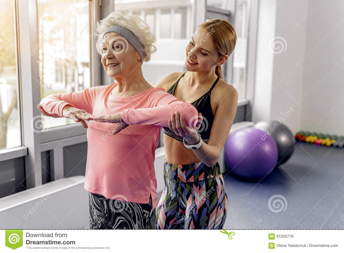 Smiling granny doing exercises with trainer