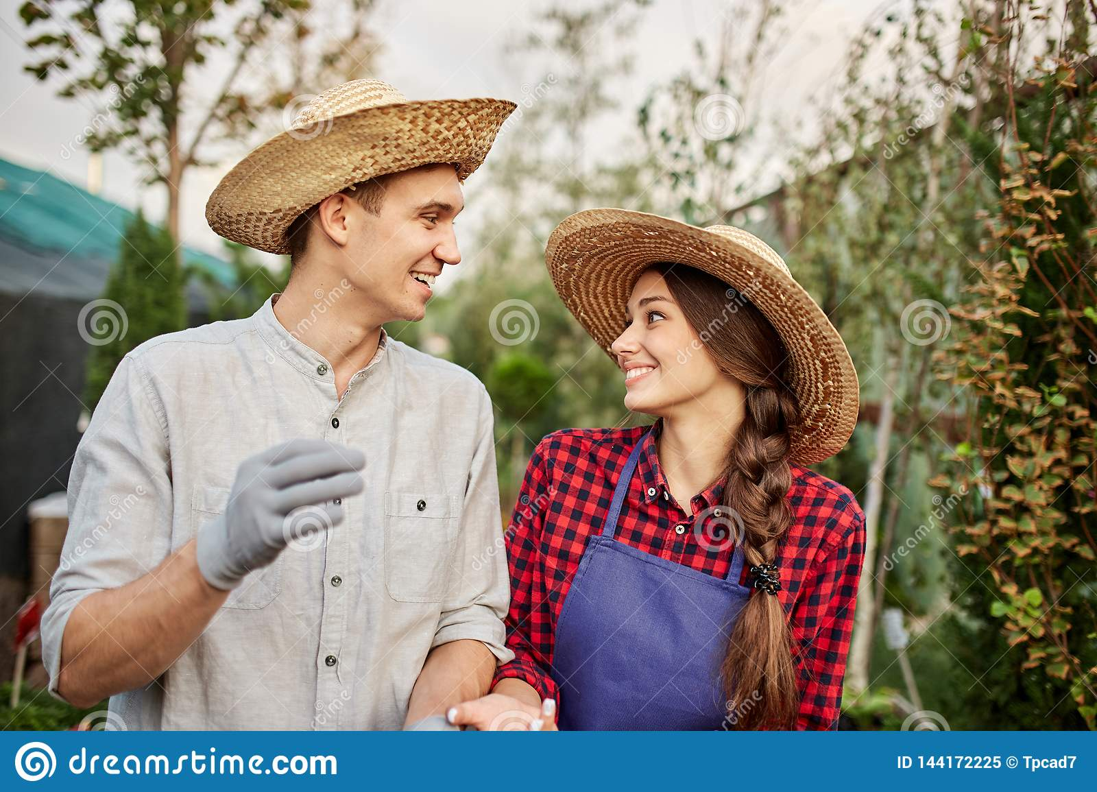 Smiling guy and girl gardeners in a straw hats look to each other in garden on a sunny day.