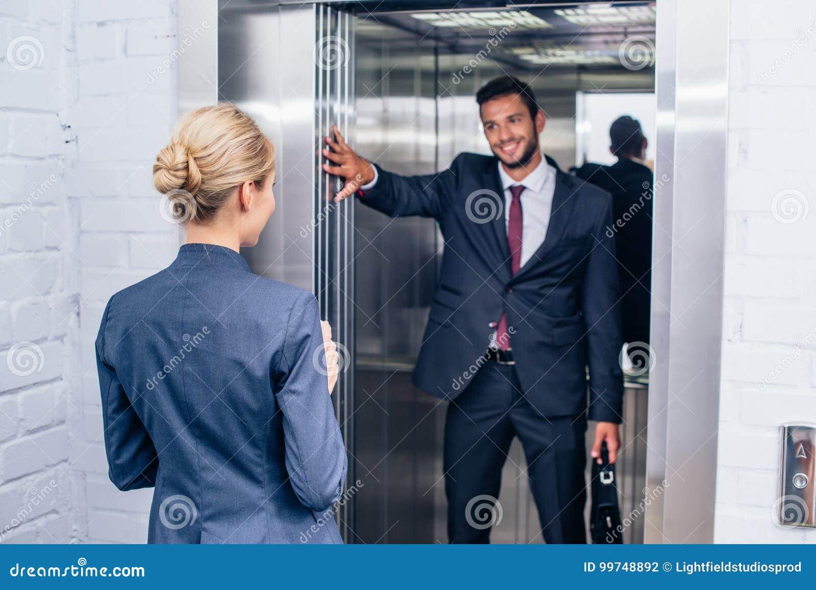 Businessman holding elevator door for woman