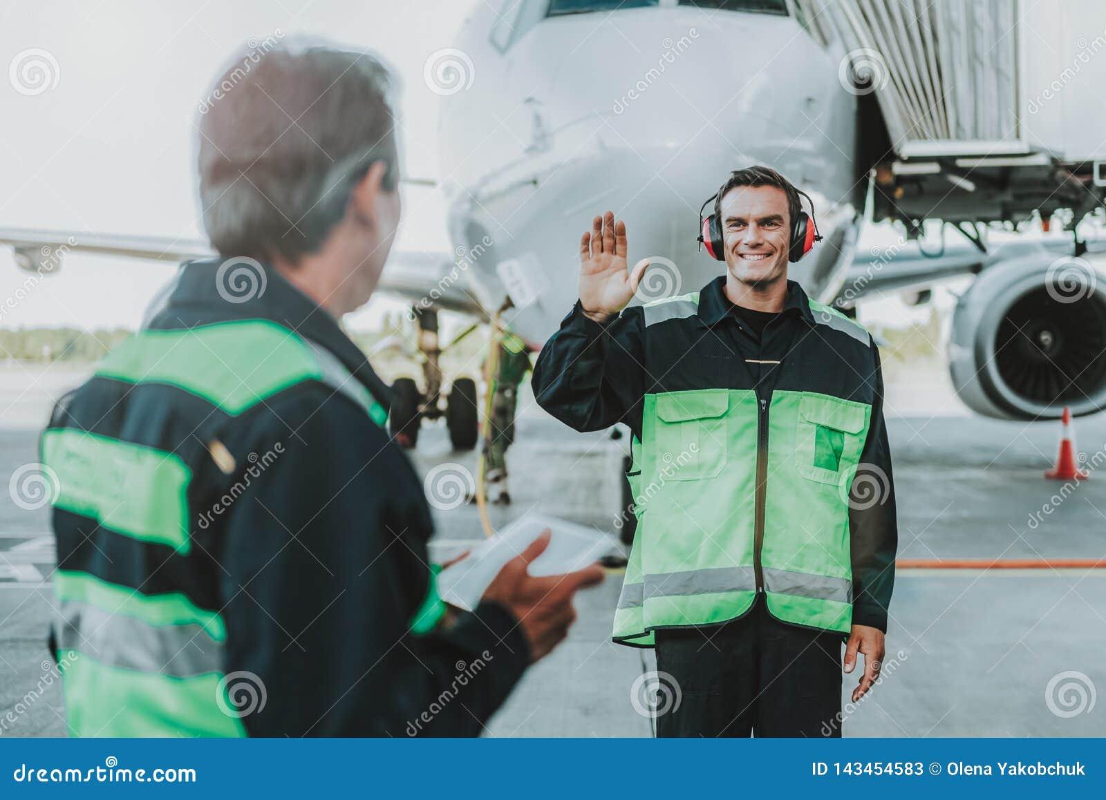 Smiling handsome employee in red headphone waving hands to mechanic