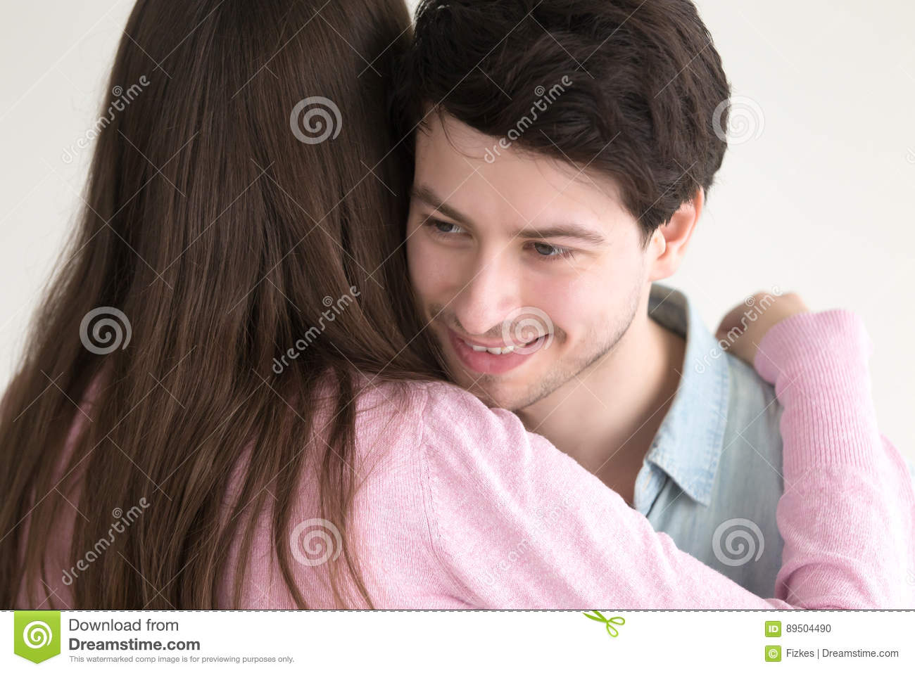 Smiling handsome guy embracing young lady, couple hugging on dat
