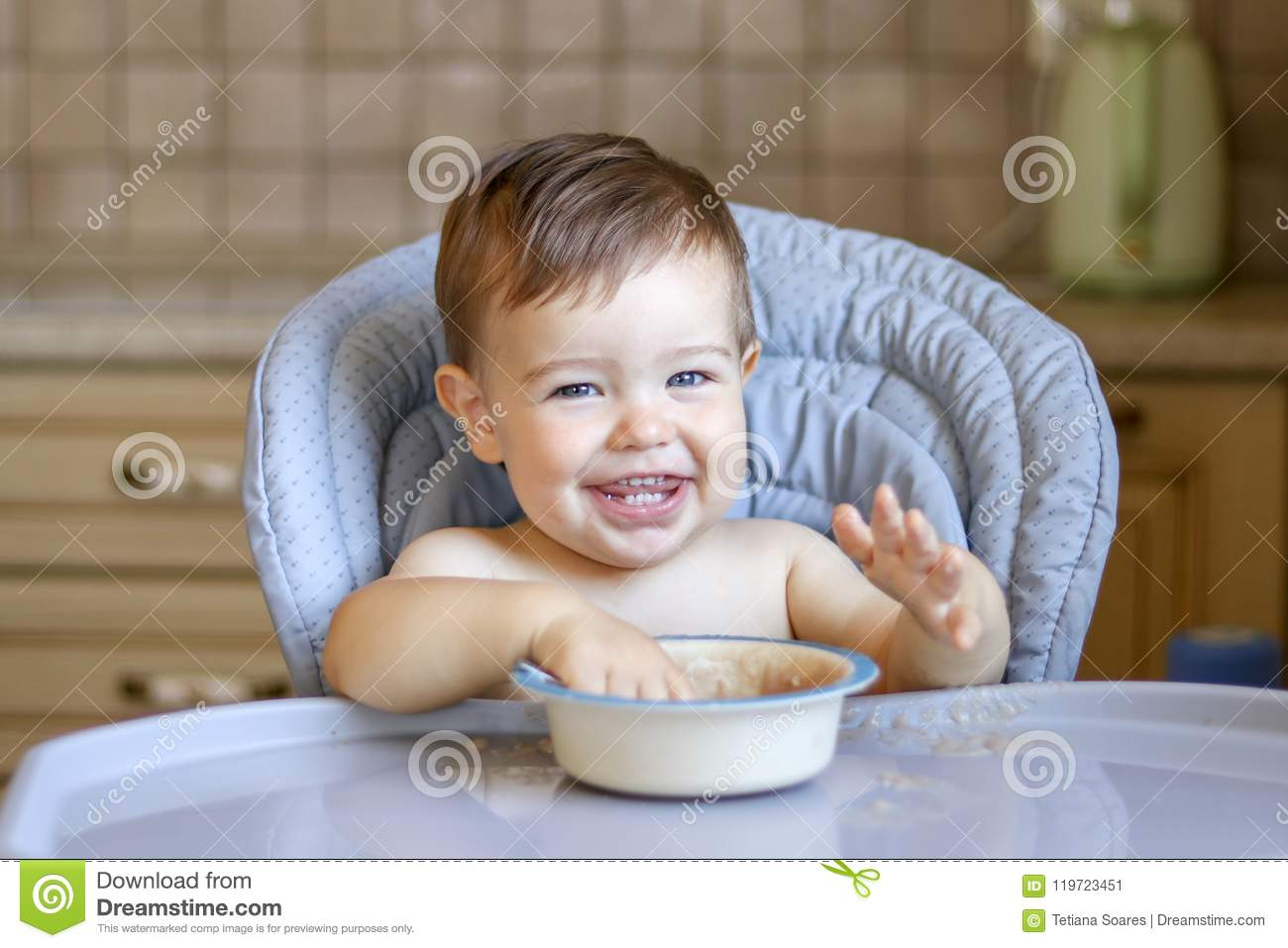 Smiling happy baby boy with eight teeth eating porridge wit his hands looking at camera sitting at high feeding chair at kitchen