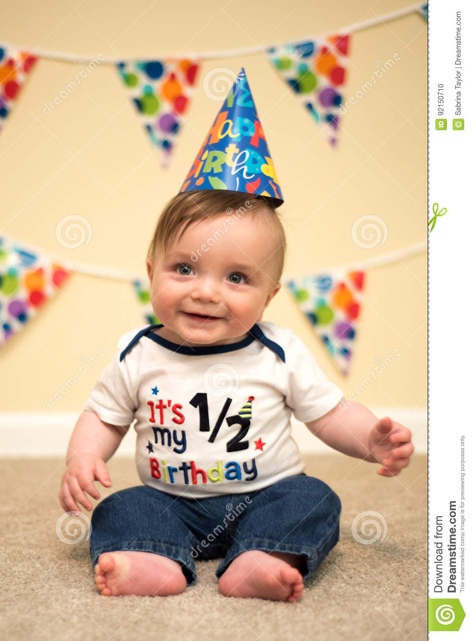 Adorable 6 Month Old Blue Eyed Baby Boy Smiling While Looking At The Camera He Is Sitting Beige Carpet With Birthday Streamers And A Yellow Wall In