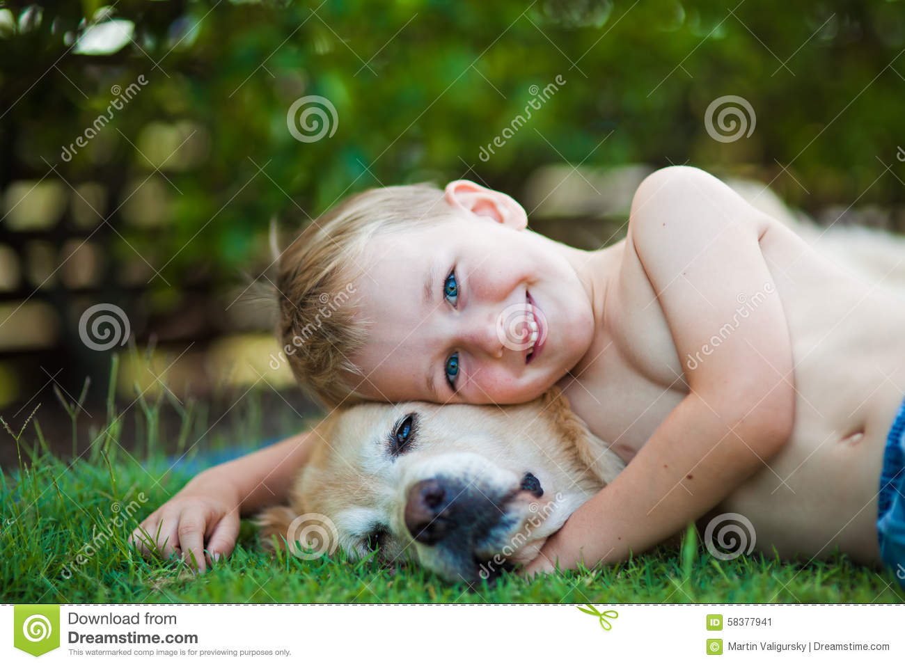 Smiling happy boy and his golden retriever in the grass