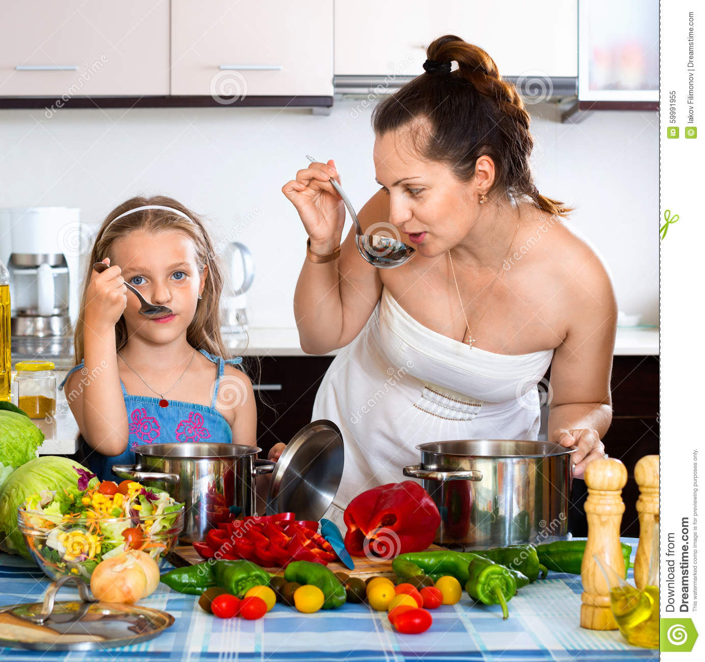 Smiling Happy Girl Helping Mother To Cook Stock Image