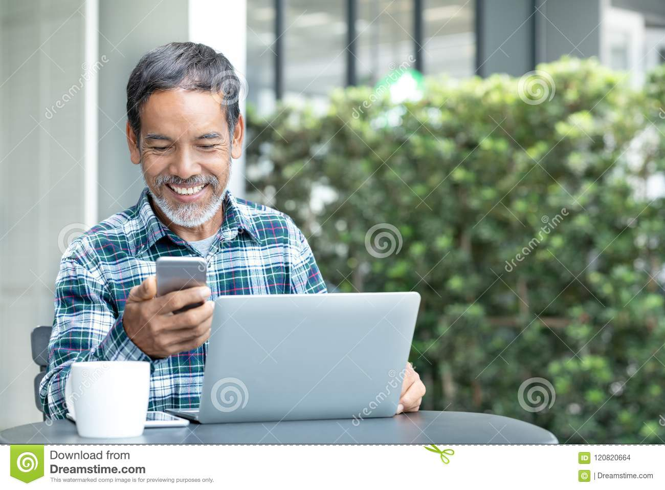 Smiling happy mature man with white stylish short beard using smartphone gadget serving internet