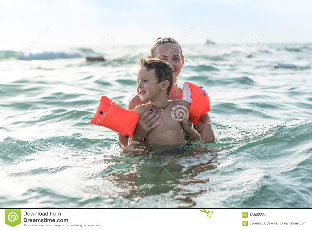 Smiling and happy mother and her son playing and running on the beach. Concept of friendly family