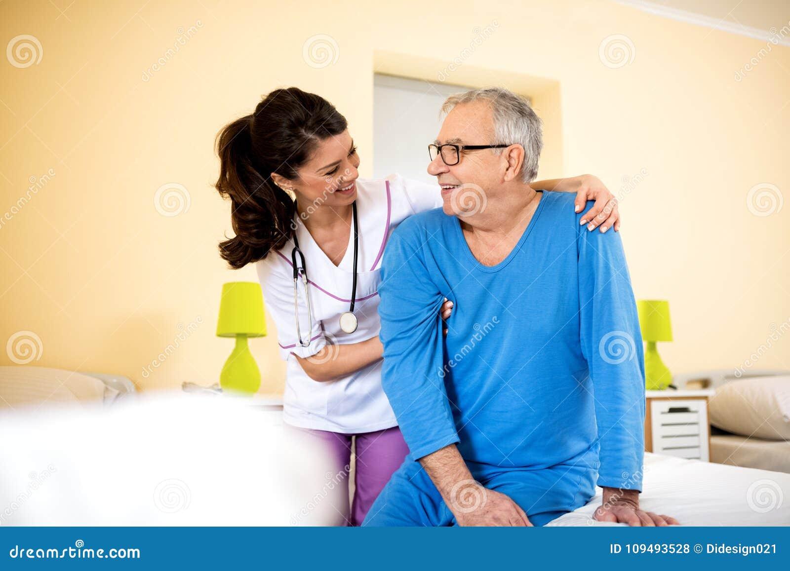 65e4a105f3 Smiling happy senior man nursing home smiling happy senior men young nurse  nursing home nurse giving