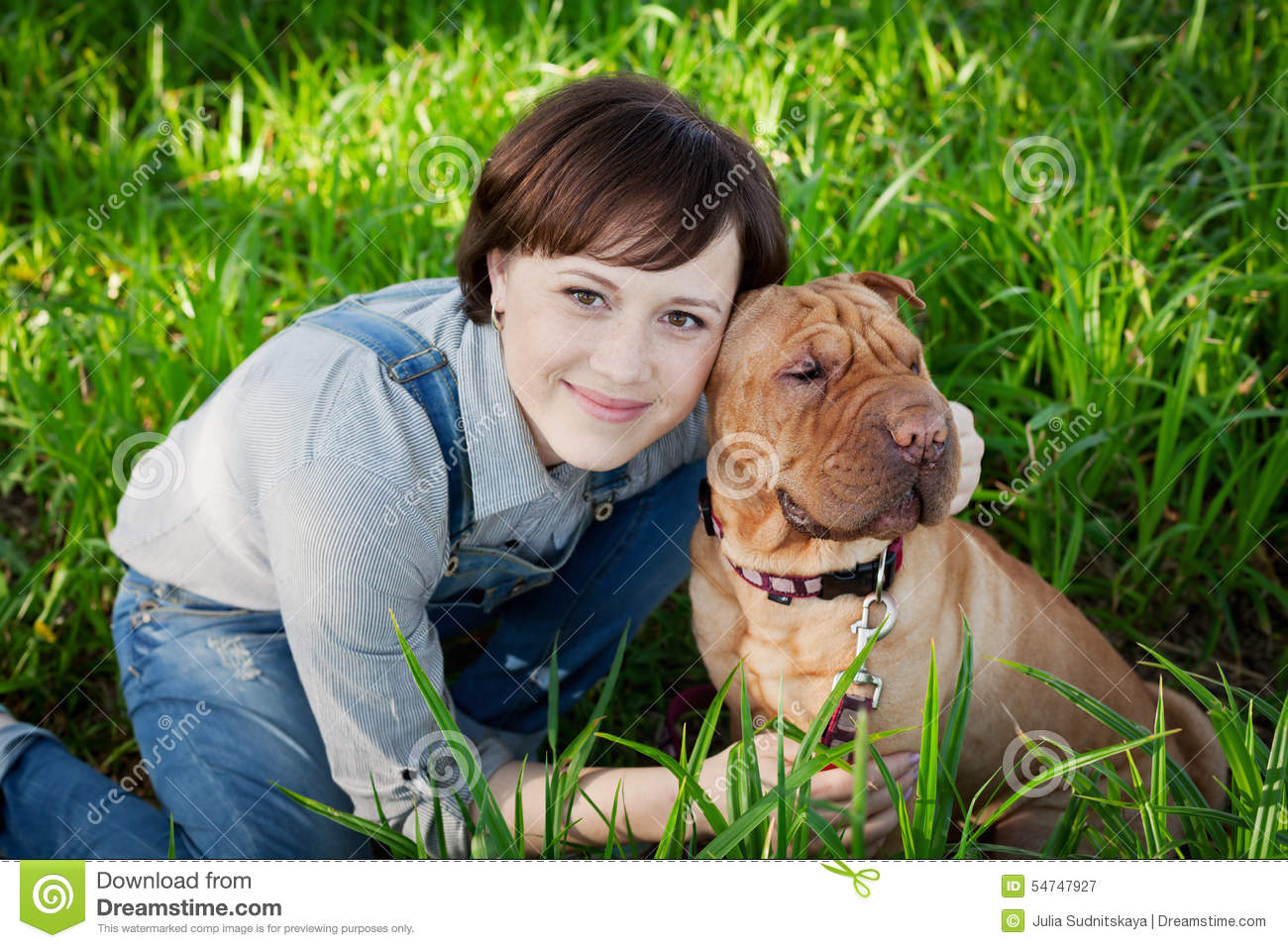 Smiling happy young woman in denim overalls hugging her red cute dog Shar Pei in the green grass in park, true friends forever
