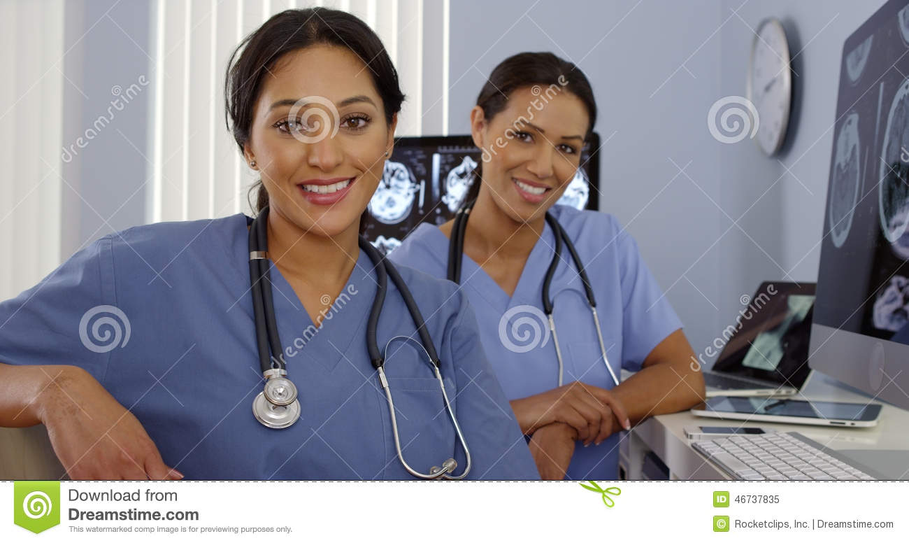Smiling Hispanic and African American nurses sitting at computer station