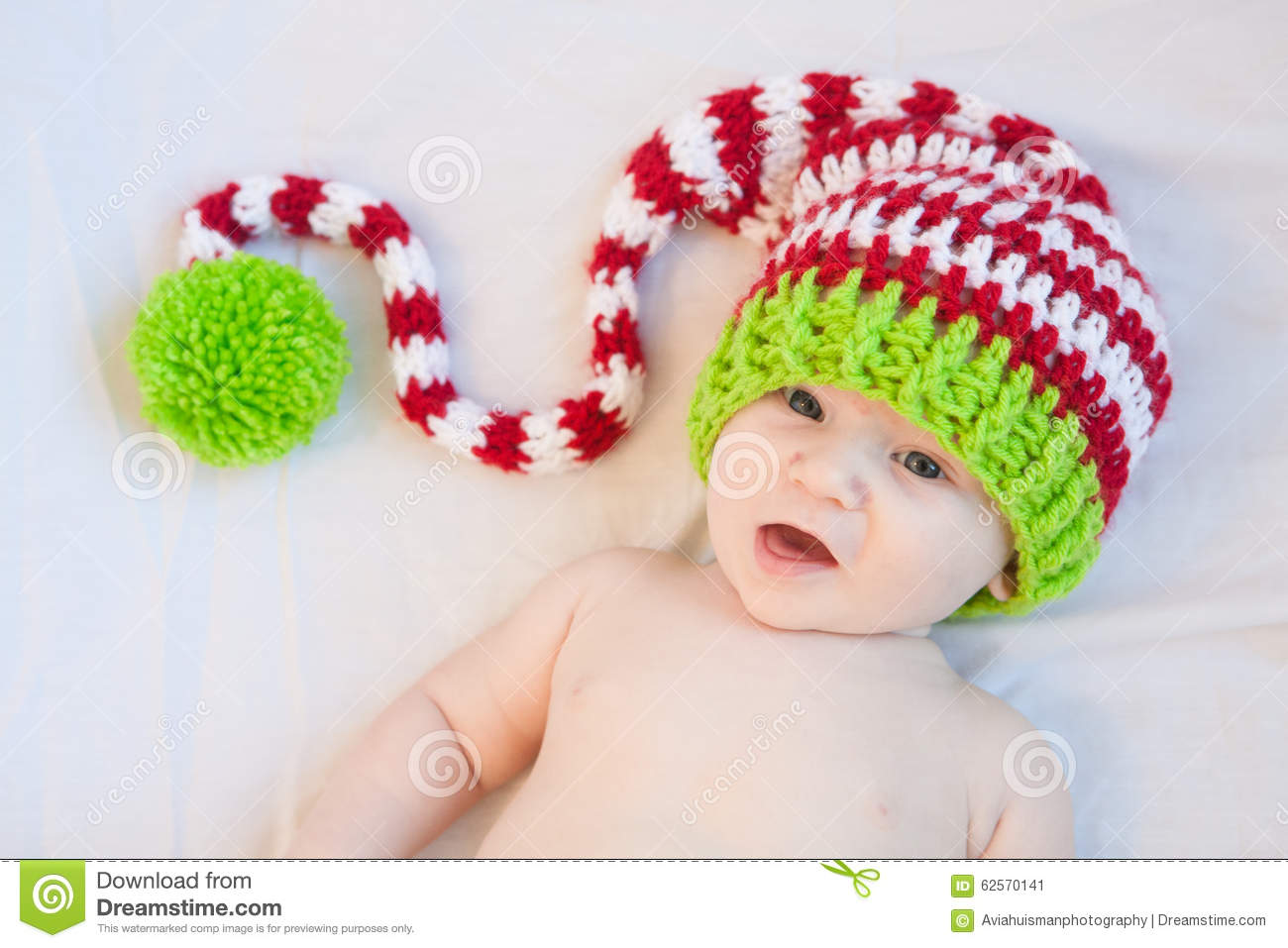 558e7e26f74 Baby wearing red white and green striped knit hat.