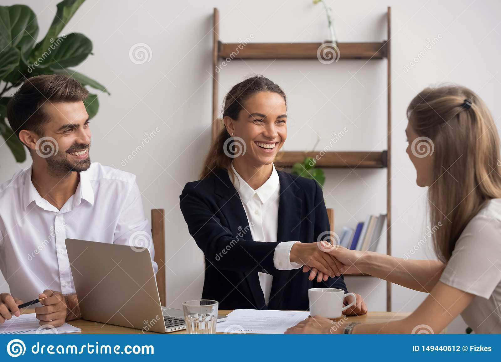 Smiling HR agent shaking hand congratulating candidate with successful interview