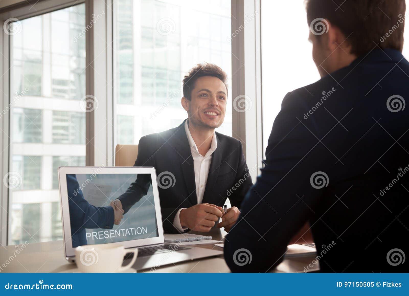 Smiling investment broker showing presentation on laptop screen