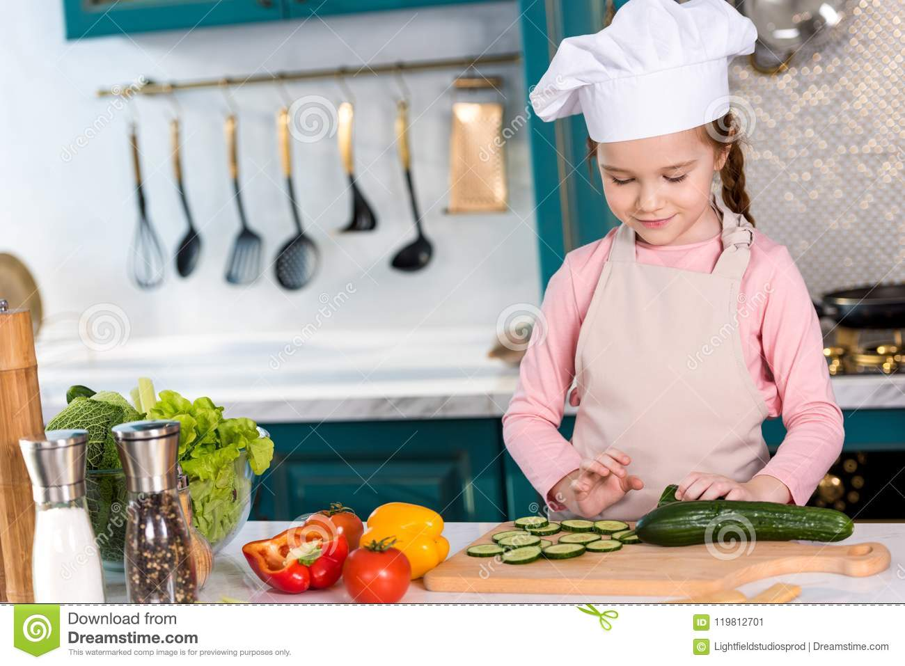 Smiling Kid In Chef Hat And Apron Cooking Vegetable Salad Stock
