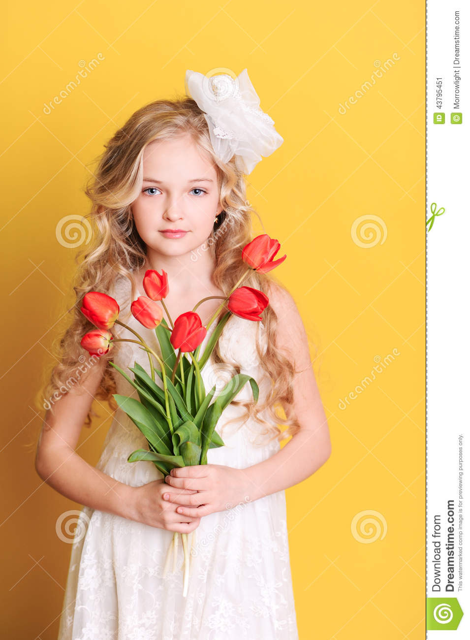 Smiling Kid Girl Holding Flowers On Yellow Stock Image ...