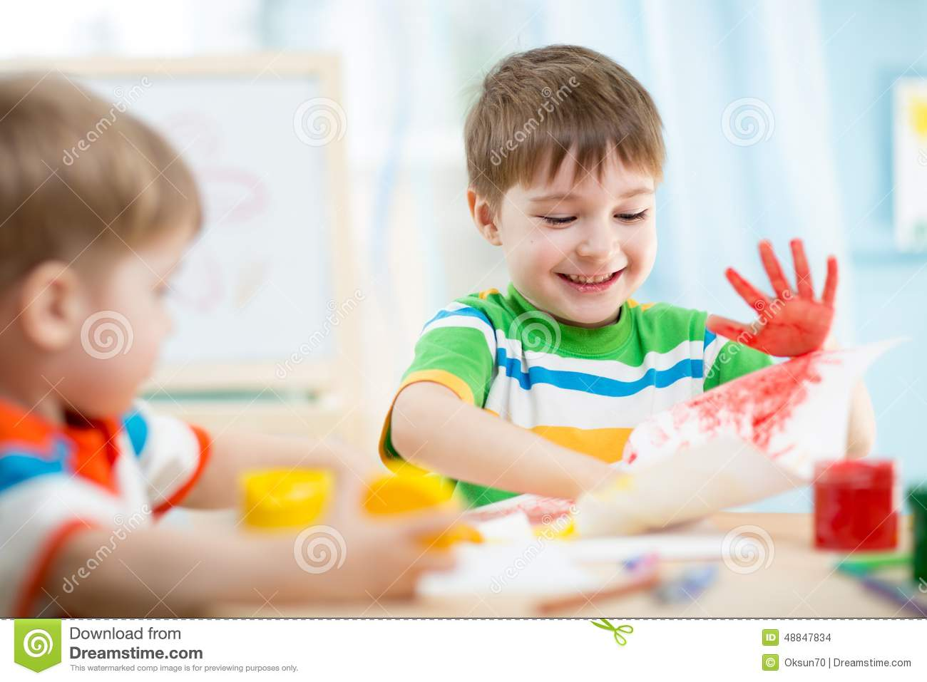 Kinder Garden: Smiling Kids Playing And Painting Stock Photo