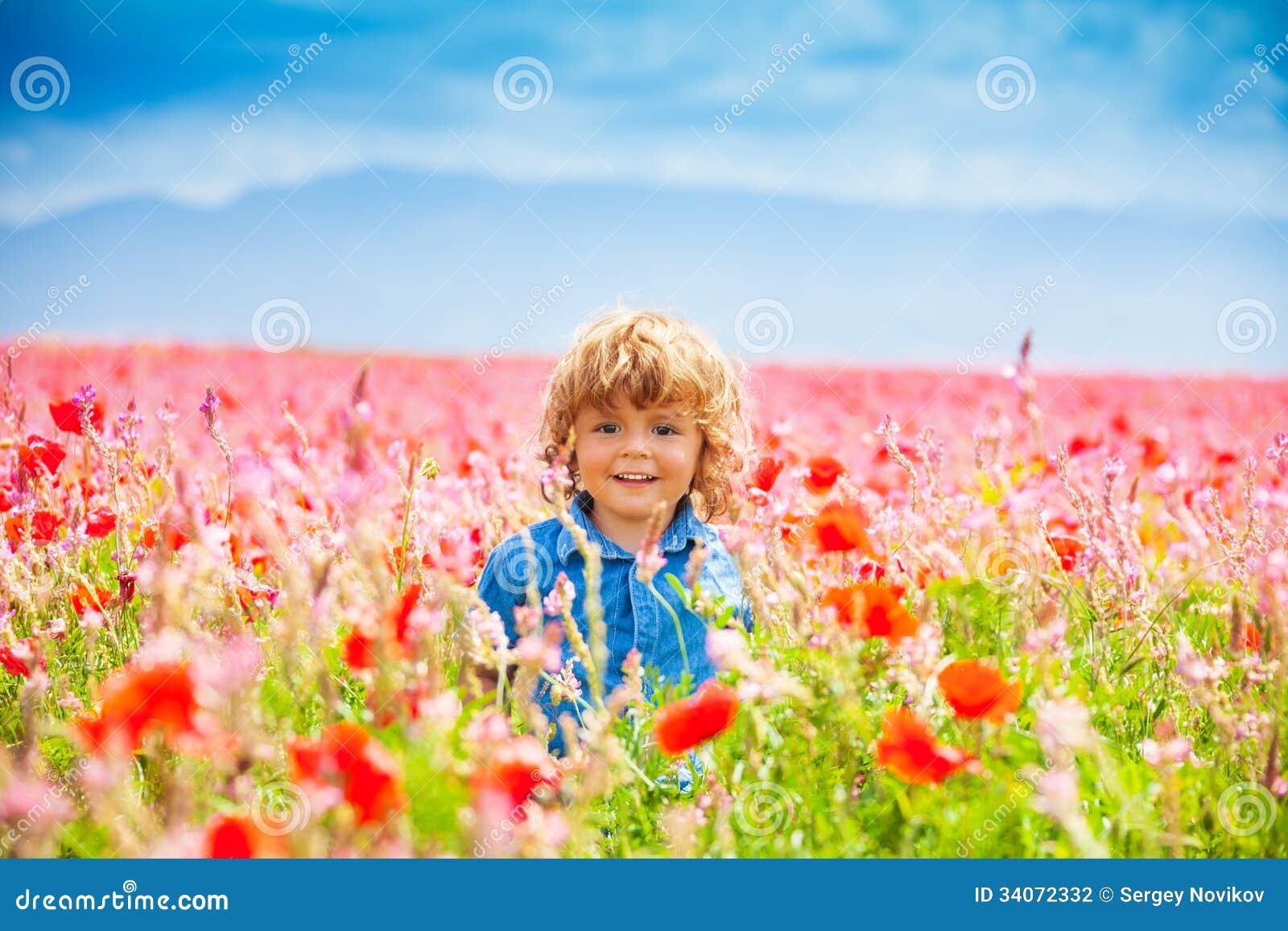 Smiling little boy in poppy field