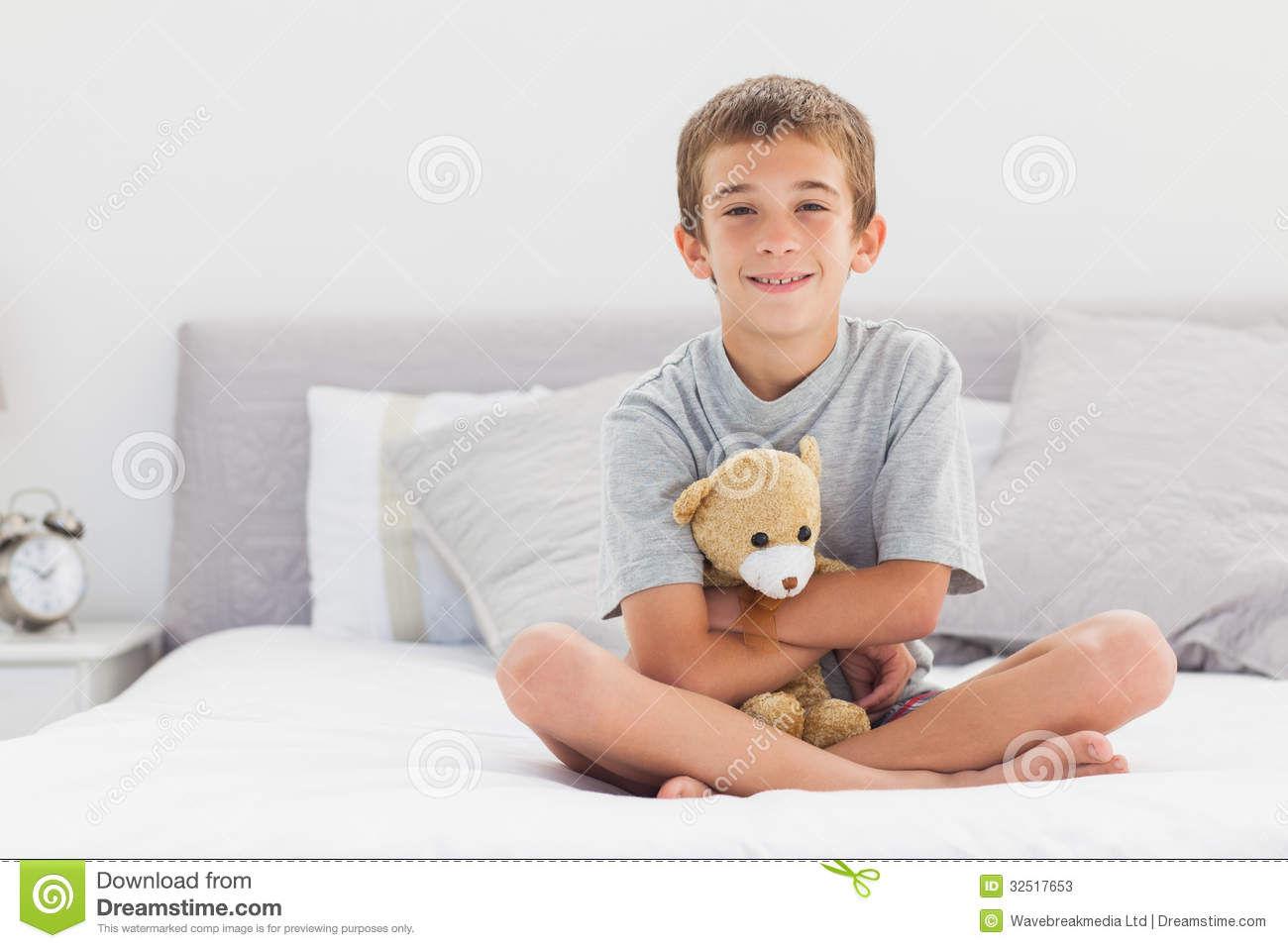 smiling little boy sitting on bed holding his teddy bear stock photos image 32517653. Black Bedroom Furniture Sets. Home Design Ideas
