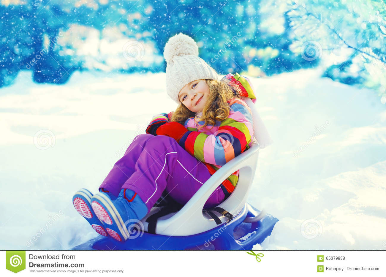 Smiling little child sitting on sled in winter