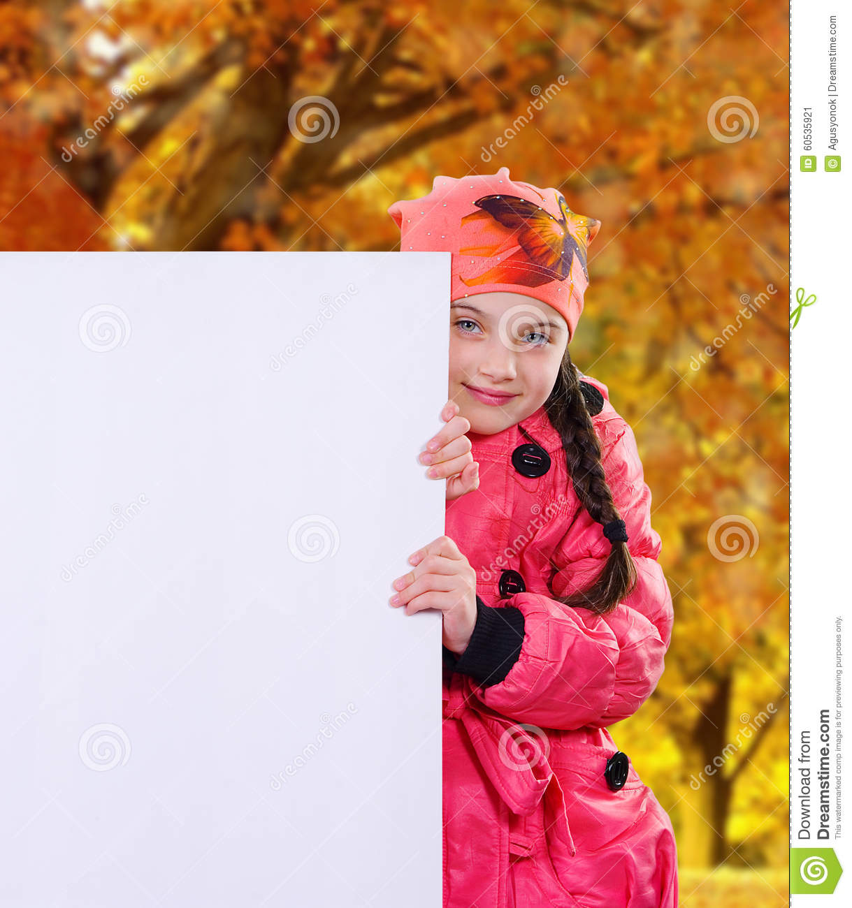 Smiling little girl child in autumn clothes jacket coat and hat holding a blank billboard banner white board.