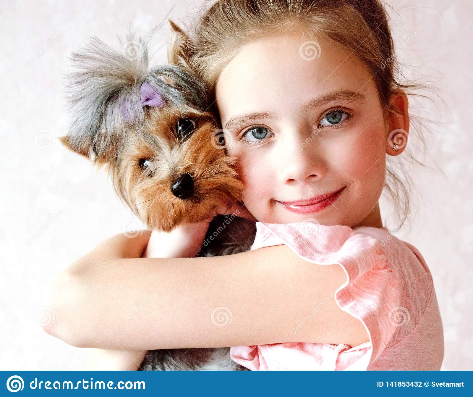 Smiling little girl child holding and playing with puppy yorkshire terrier