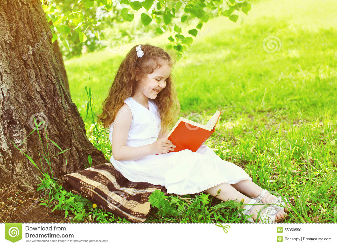 Smiling Little Girl Child Reading A Book On The Grass Near ...