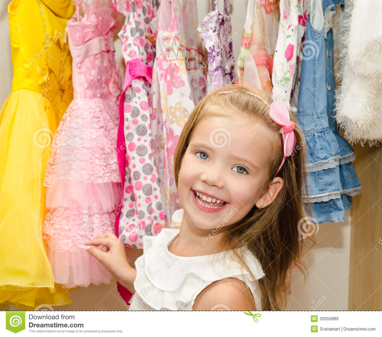 dd4631010 Smiling Little Girl Chooses A Dress From The Wardrobe Stock Image ...