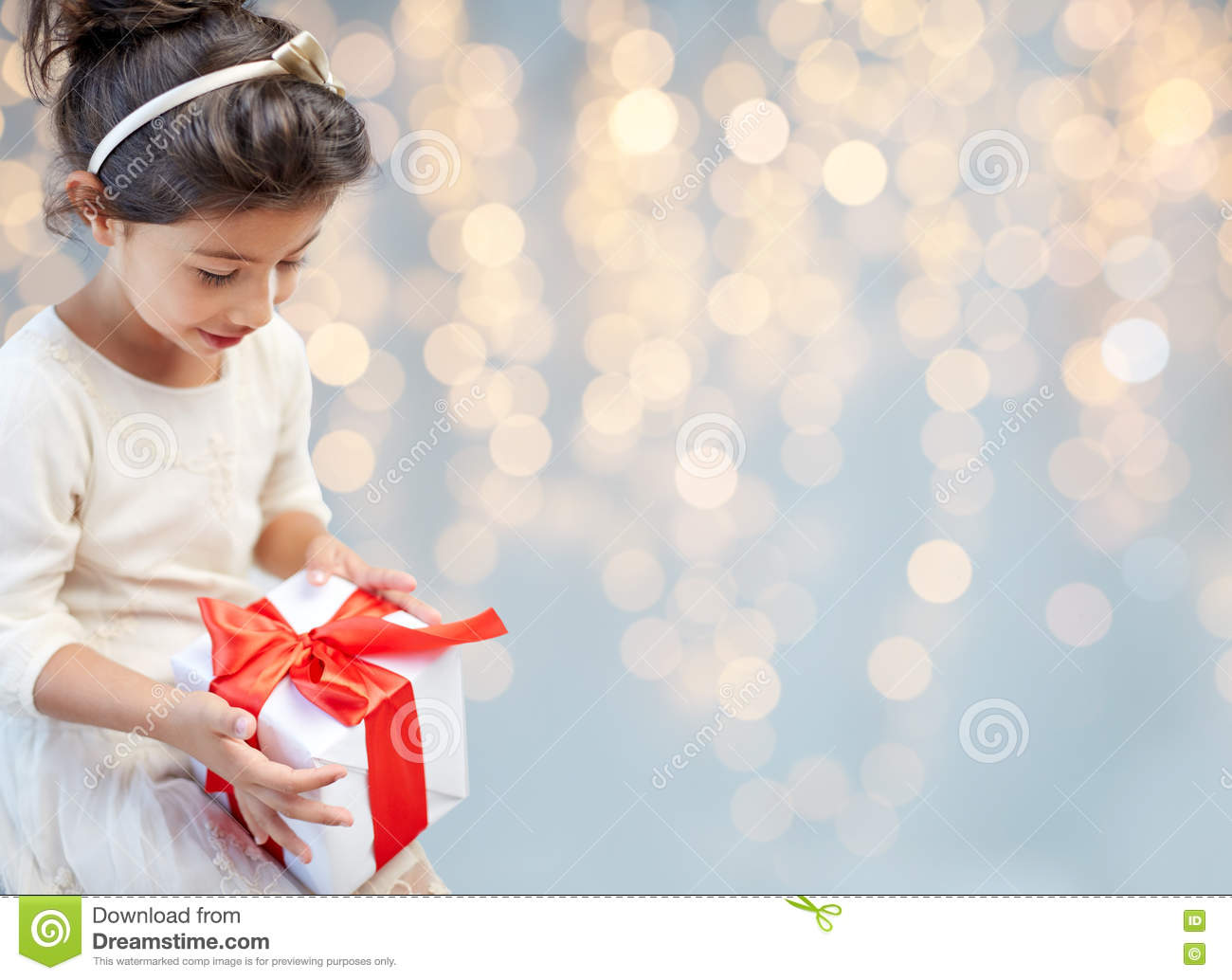 Smiling little girl with gift box over lights