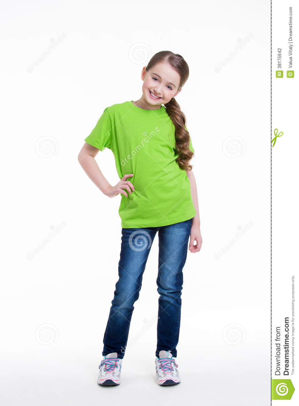 Portrait of a smiling little girl in a green shirt and blue jeans on a ...